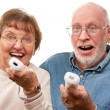 Royalty-Free Stock Photo: Happy Senior Couple Play Video Game with Remotes