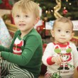 Baby and Young Boy Enjoying Christmas Morning Near The Tree — Stock Photo