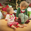Baby and Young Boy Enjoying Christmas Morning Near The Tree — Stock Photo #16977909