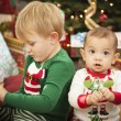 Royalty-Free Stock Photo: Mixed Race Baby and Young Boy Enjoying Christmas Morning Near Th