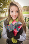 Pretty Woman with Wrapped Gift with Bow Outside — Stock Photo