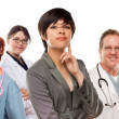 Stock Photo: Young Mixed Race Woman with Doctors and Nurses Behind