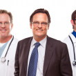Smiling Businessman with Doctors and Nurses - Stock Photo