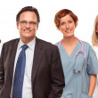 Stock Photo: Smiling Businessman with Doctors and Nurses