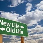 新しい生活、雲の上の古い緑の生活道路標識 — ストック写真