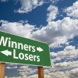 Winners, Losers Green Road Sign Over Clouds - Stock Photo