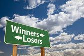 Vencedores, sinal de estrada perdedores verde sobre nuvens — Foto Stock