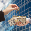 Handing Stack of Cash For Key and Corporate Building — Stock Photo