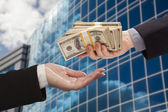 Male Handing Stack of Cash to Woman with Corporate Building — Stock Photo
