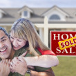 Mixed Race Couple in Front of Sold Real Estate Sign and House - Stock Photo