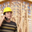 Hispanic Male Contractor on Phone in Front of House Framing — Stock Photo