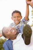 Mieszanej rasy ojciec i syn gra piggyback — Zdjęcie stockowe