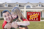 Mixed Race Couple in Front of Sold Real Estate Sign and House — Stock Photo