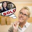 Woman in Empty Room with Thought Bubble of Sold Real Estate Sign - Foto Stock