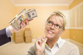 Woman Being Handed Stacks of Money in Empty Room — Stock Photo