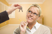 Woman Being Handed Keys in Empty Room with Boxes — Stock Photo