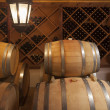 Wine Barrels and Bottles in Cellar - Stock Photo