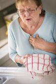 Mujer adulta senior en el fregadero con dolores en el pecho — Foto de Stock