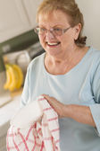 Senior Adult Woman Drying Bowl At Sink in Kitchen — Stock Photo