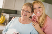 Senior Adult Woman and Young Daughter Portrait in Kitchen — Stock Photo