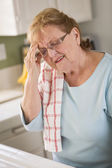 Senior Adult Woman At Kitchen Sink With Head Ache — Stockfoto