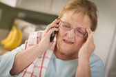 Shocked Senior Adult Woman on Cell Phone in Kitchen — Stock Photo