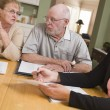 Senior Adult Couple Going Over Papers in Their Home with Agent - Stock Photo