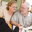 Stock Photo: Senior Adult Couple Going Over Papers in Their Home with Agent