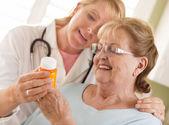 Kvinnliga läkare eller sjuksköterska förklarar recept till senior vuxna w — Stockfoto