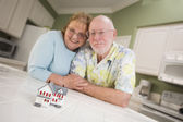 Senior Adult Couple Gazing Over Small Model Home on Counter — Stockfoto