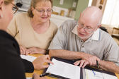 Senior Adult Couple Going Over Papers in Their Home with Agent — Foto Stock