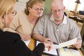 Couple d'adultes principal aller sur papiers dans leur maison avec l'agent — Photo