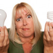 Confused Blonde Holds Energy Saving Lightbulb — Stock Photo #2345247