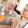 Doctor or Nurse Explaining Prescription Medicine to Senior Man - Stock Photo