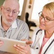 Doctor or Nurse Talking to Senior Man with Touch Pad — Stockfoto