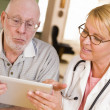 Foto Stock: Doctor or Nurse Talking to Senior Man with Touch Pad