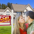 Couple in Front of Real Estate Sign and House - Stock Photo