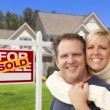 Foto Stock: Couple in Front of Sold Real Estate Sign and House
