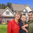 Royalty-Free Stock Photo: Mixed Race Young Family in Front of House