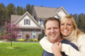 Happy Couple Hugging in Front of House — Stock Photo