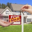 Stock Photo: Agent Handing Over House Keys in Front of New Home