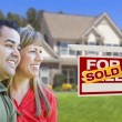 Couple in Front of Sold Real Estate Sign and House — Stock Photo #24281165