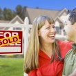 Couple in Front of Sold Real Estate Sign and House — Stock Photo #24281241