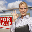 Businesswoman In Front of Office Building and For Sale Sign - Stock Photo