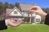 Agente de entrega de las llaves de casa frente a su casa nueva — Foto de Stock