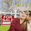 Couple in Front of For Sale Sign and House - Stock Photo