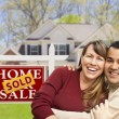 Couple in Front of Sold Real Estate Sign and House - Stock Photo