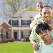 African American Family In Front of Beautiful House - Stock Photo