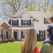 Mixed Race Young Family Looking At Beautiful Home — Stock Photo #24418331