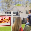 Stock Photo: Family Facing Sold For Sale Real Estate Sign and House